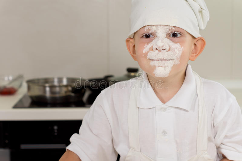 Cute little boy cook with a face full of flour. Cute little boy cook in a chefs toque with a face full of flour smiling at the camera as he stands in front of stock photo