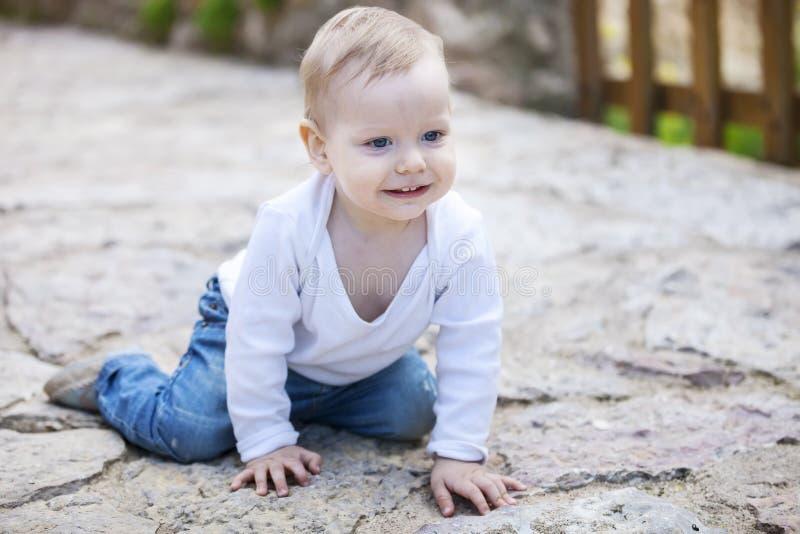 Cute little boy crawling on stone paved sidewalk stock photography