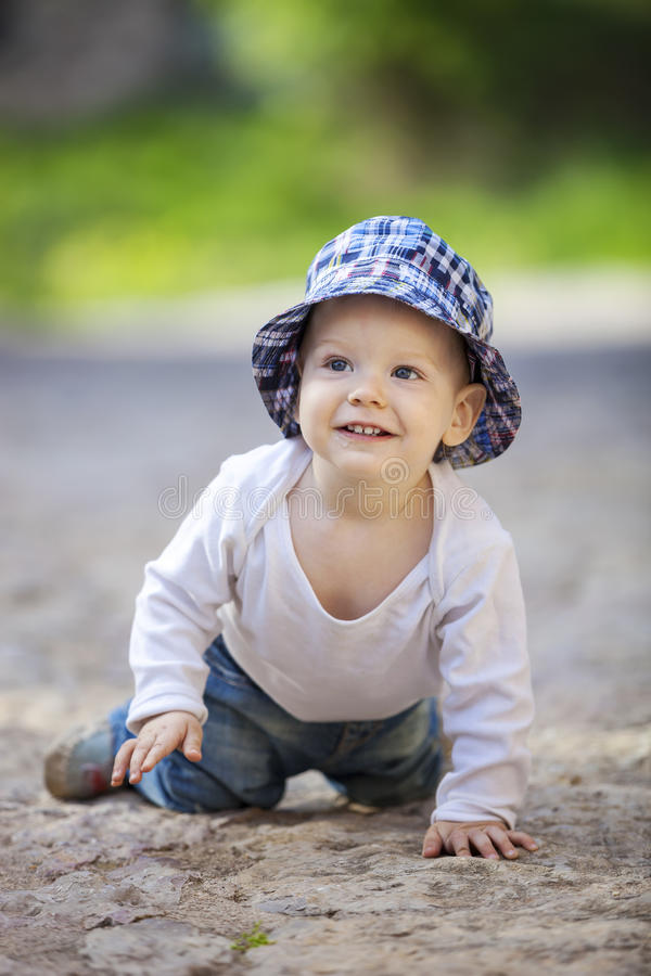 Cute little boy crawling on stone paved sidewalk stock photos