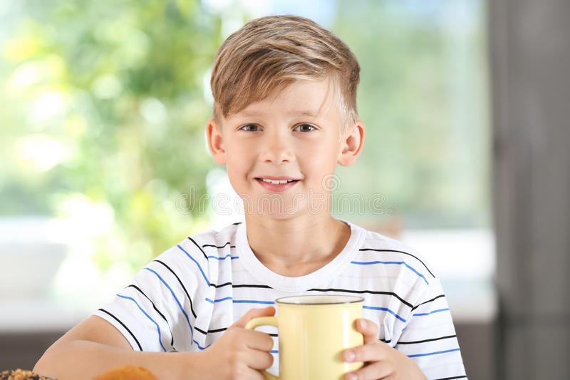 Cute little boy with cup of hot cocoa drink at home stock photo