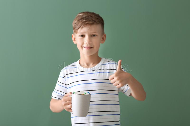 Cute little boy with cup of hot cocoa drink showing thumb-up gesture on color background stock image