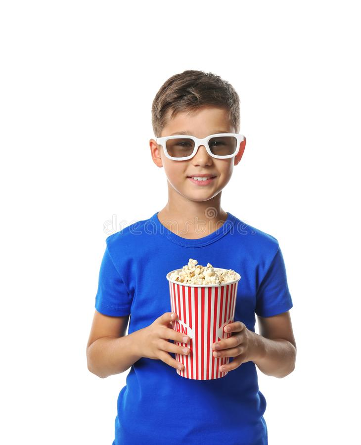 Cute little boy with cup of popcorn wearing 3D cinema glasses on white background stock images