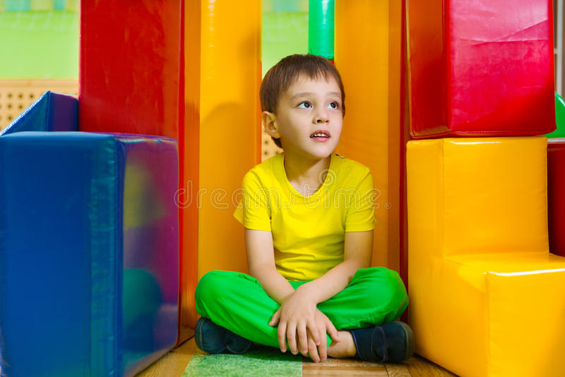 Cute little boy in daycare gym. Cute little boy sitting on floor in daycare gym stock photos