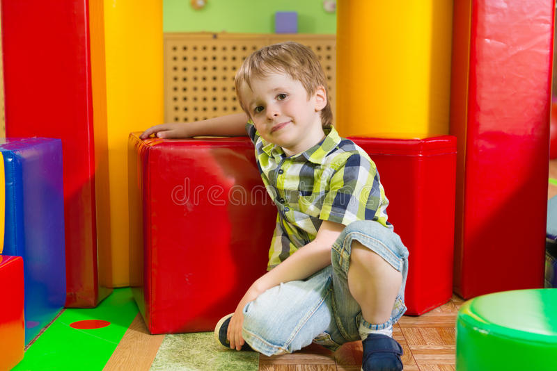 Cute little boy in daycare gym. Cute little boy sitting on floor in daycare gym stock photography