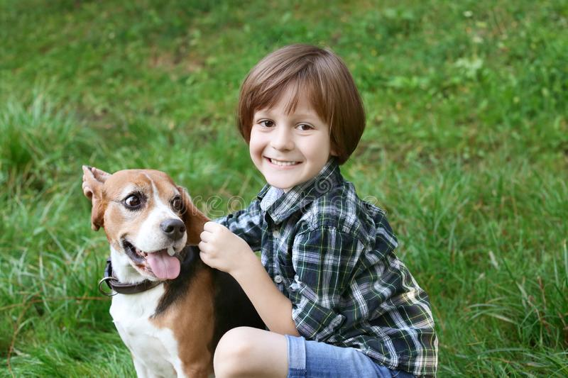 Cute little boy with dog resting in green park stock photo