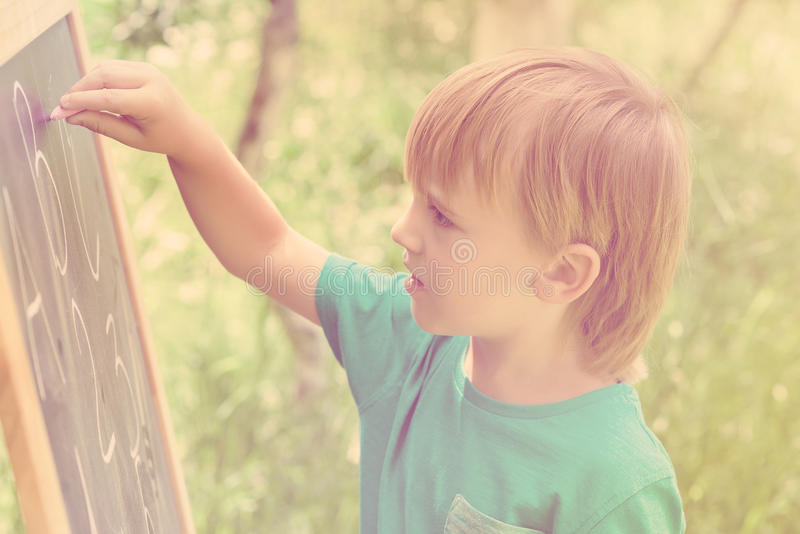 Cute little boy drawing on blackboard with chalk, outdoor on summer sunny day. Toned. stock photography