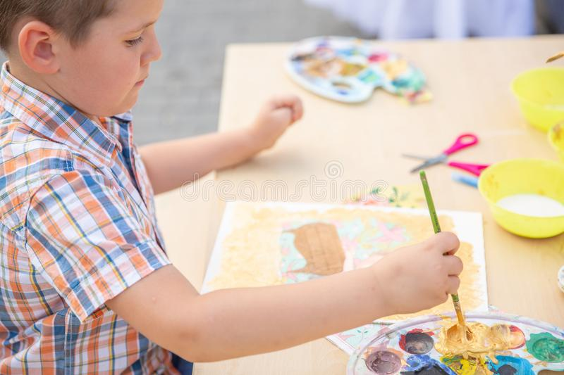 Cute little boy drawing with colorful paints in fall park. Creative child painting on nature. Outdoors activity for toddler kid. royalty free stock images