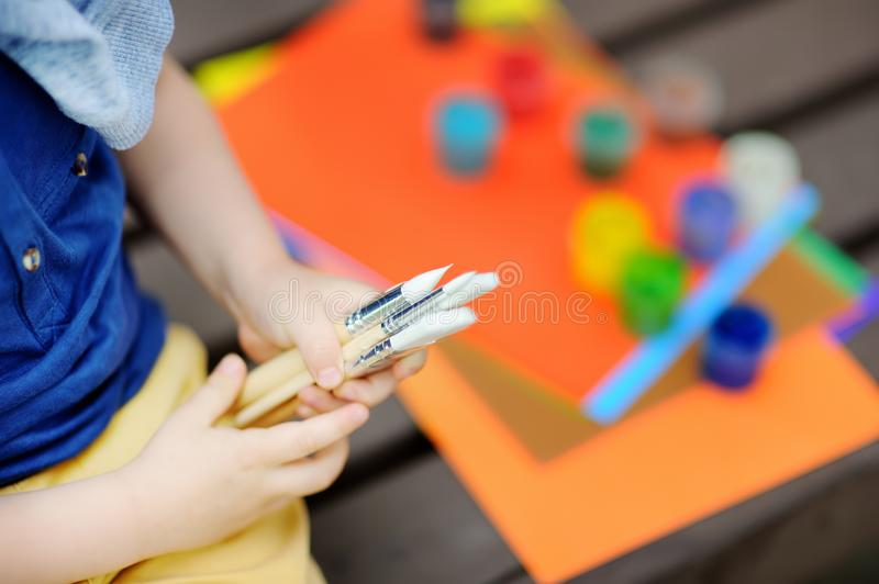 Cute little boy drawing with colorful paints in summer park royalty free stock image