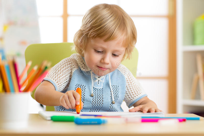 Cute little boy is drawing with felt-tip pen in preschool stock images
