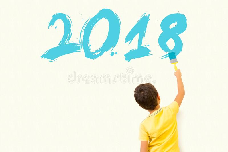 Cute little boy drawing new year 2018 with painting brush on wal royalty free stock photography
