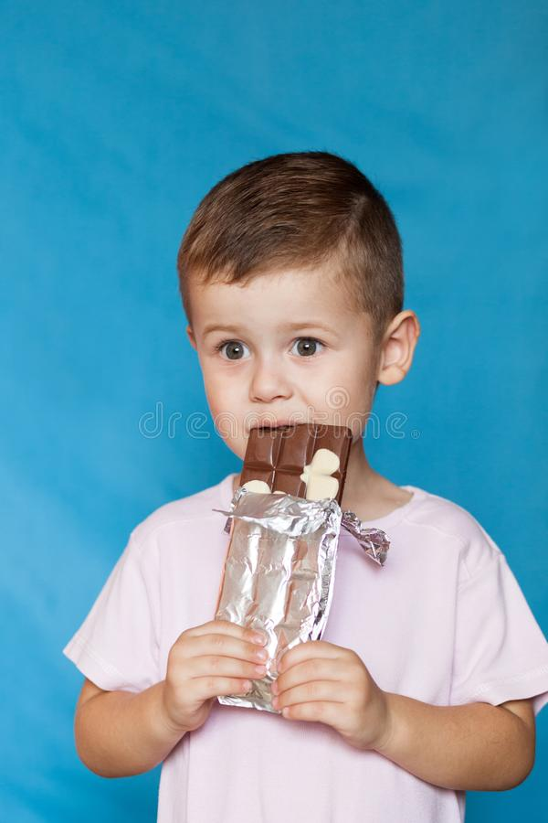 Cute Little Boy Eating Chocolate Bar. Very cute kid with chocolate, isolated. royalty free stock image