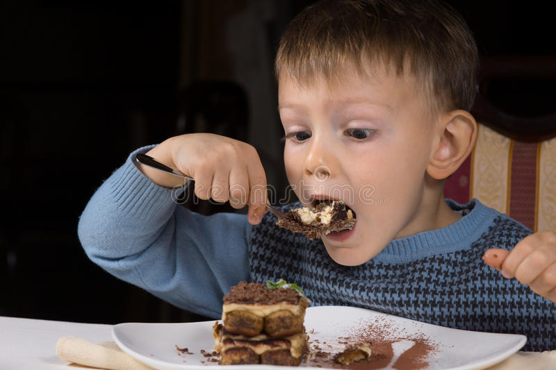 Cute little boy eating chocolate cake. About to take a big mouthful with a look of eager anticipation as he sits at table royalty free stock photo