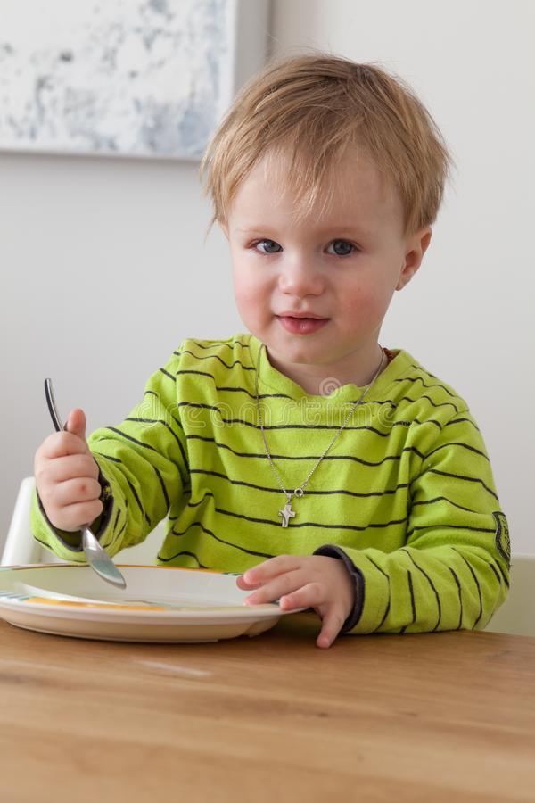 Cute little boy eating in cozy dining room. Child having a dinner at home. Healthy nutrition for small kids. stock photos