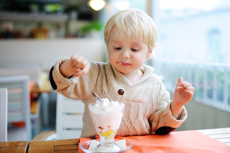 Cute little boy eating Ice-Cream gelato in Italian indoors cafe stock photos