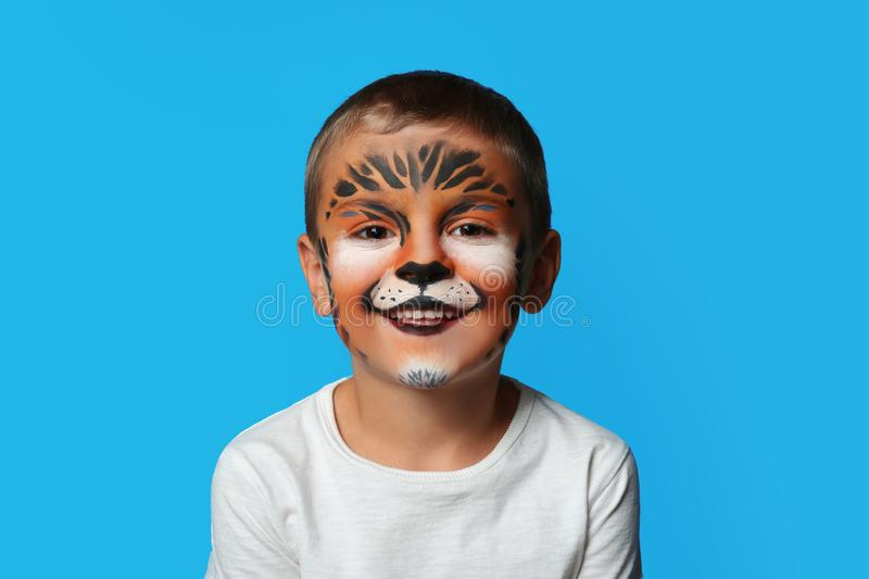 Cute little boy with face painting on background. Cute little boy with face painting on blue background royalty free stock images