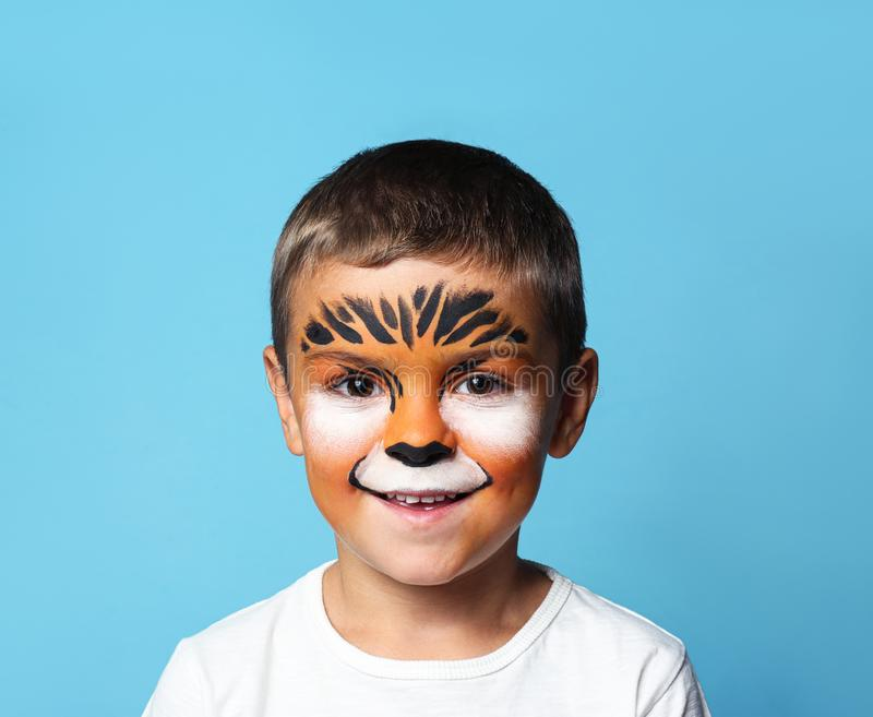 Cute little boy with face painting on background. Cute little boy with face painting on blue background royalty free stock photography