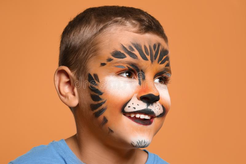 Cute little boy with face painting. On orange background stock photo