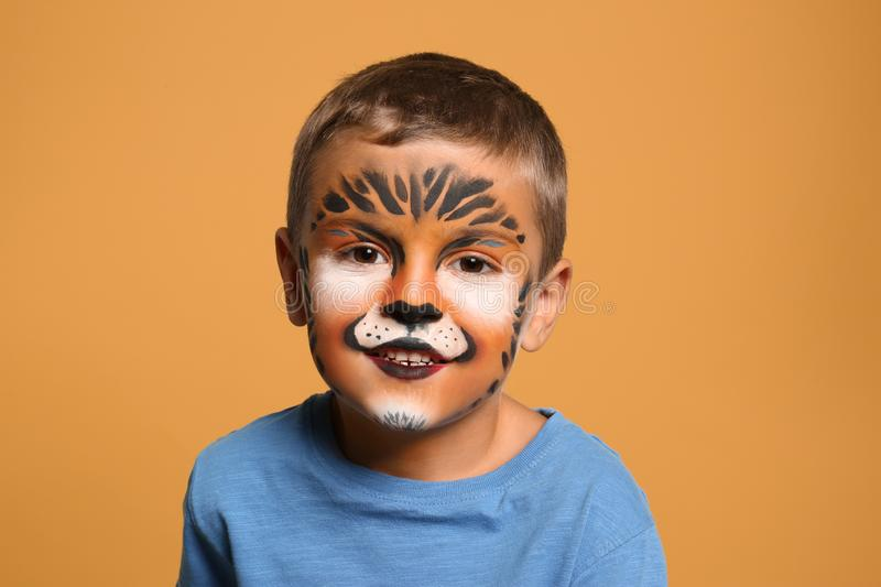 Cute little boy with face painting. On orange background stock image