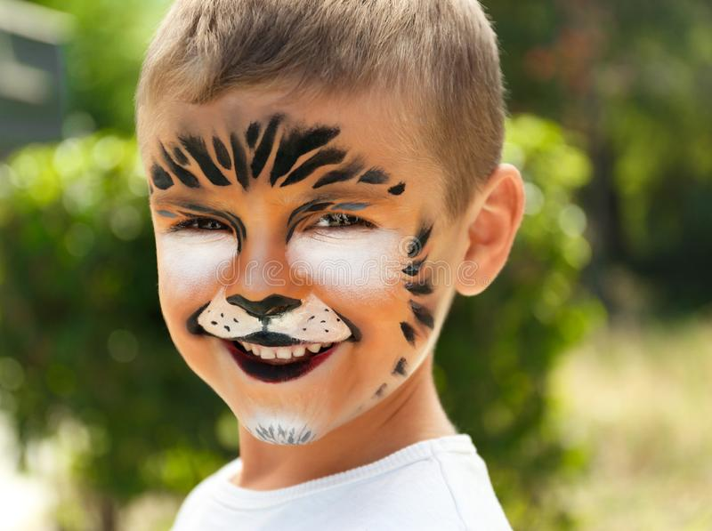 Cute little boy with face painting. Outdoors royalty free stock photos