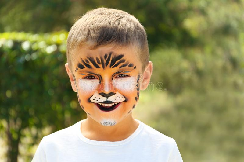 Cute little boy with face painting. Outdoors stock images