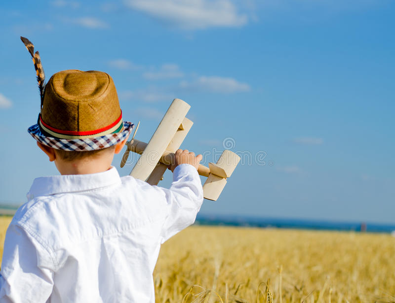 Cute little boy flying his toy biplane. Cute little boy flying his wooden toy biplane holding high above his head as he dreams about becoming pilot, blue sky royalty free stock photo