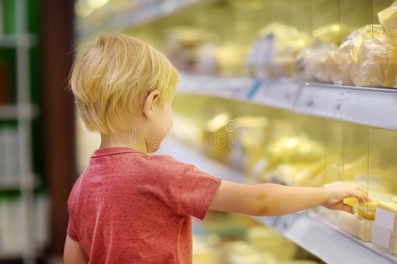 Cute little boy in a food store or a supermarket choosing cheese and butter, fresh dairy. Healthy lifestyle for family with kids. Cute little boy in a food store royalty free stock photo