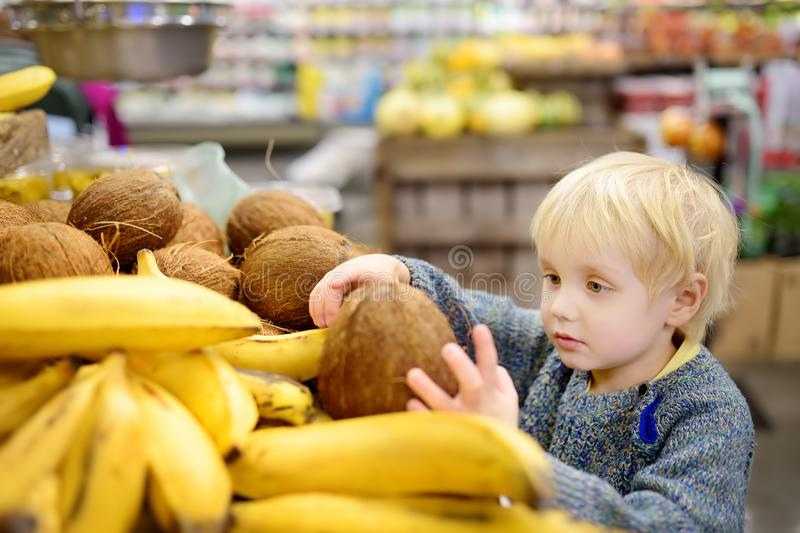 Cute little boy in a food store or a supermarket choosing fresh organic coconut. Healthy lifestyle for young family with kids stock photo
