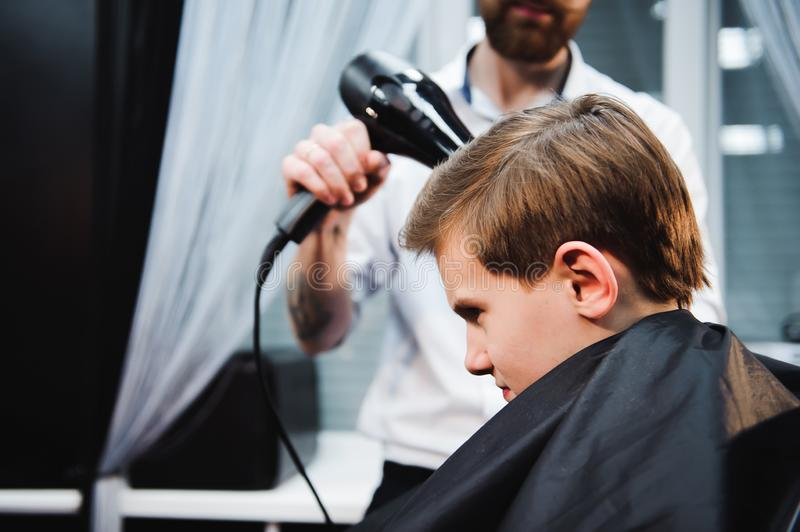Cute little boy is getting haircut by hairdresser at the barbershop. Cute little boy is getting haircut by hairdresser at the barbershop royalty free stock images
