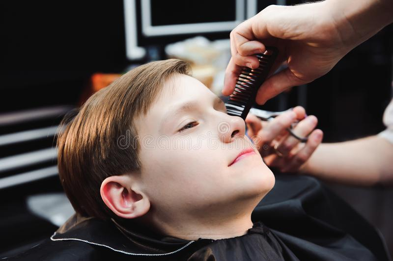 Cute little boy is getting haircut by hairdresser at the barbershop. Cute little boy is getting haircut by hairdresser at the barbershop royalty free stock photo