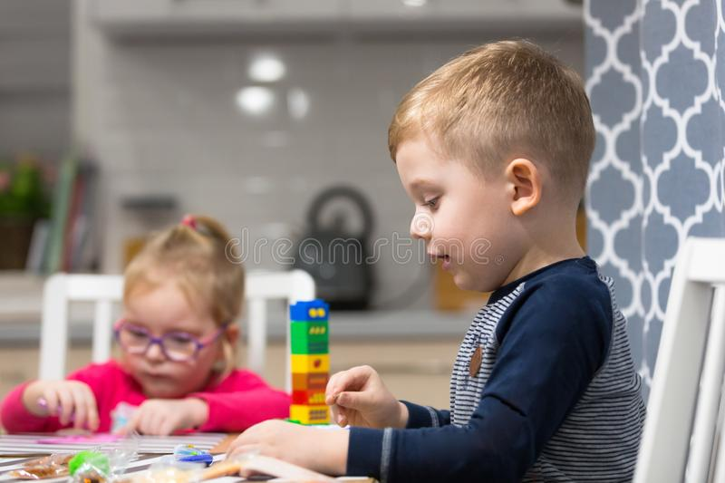 Cute little boy and girl doing preschool homework and painting stock photo
