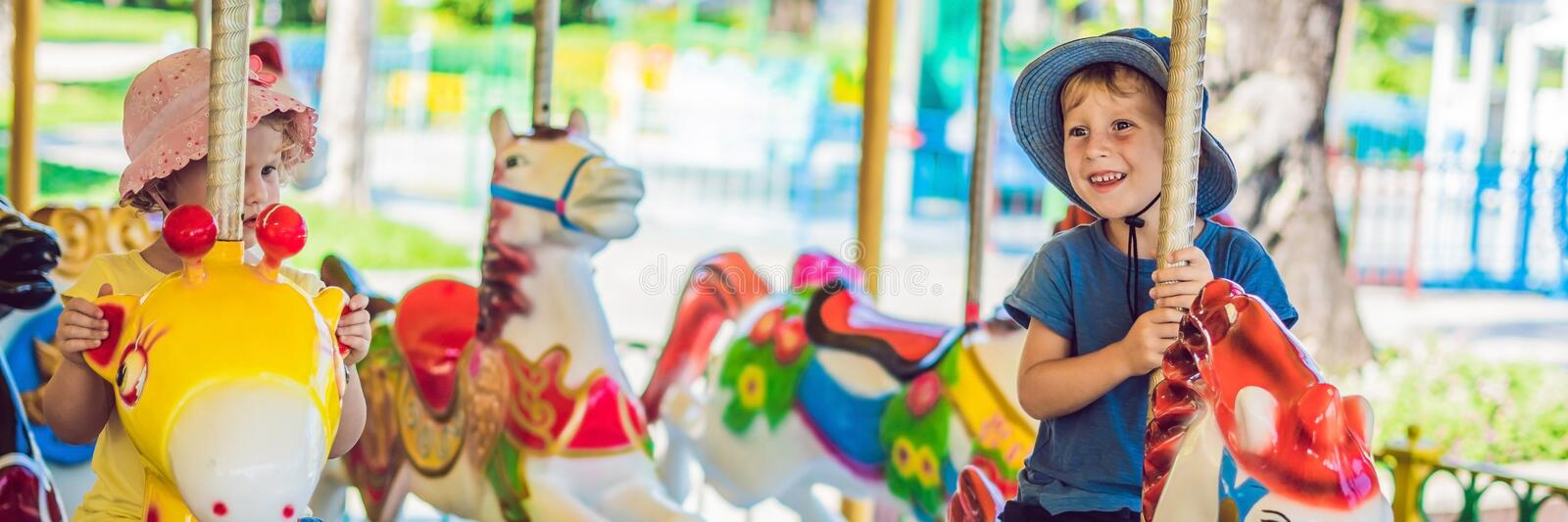 Cute little boy and girl enjoying in funfair and riding on colorful carousel house BANNER, long format stock photo