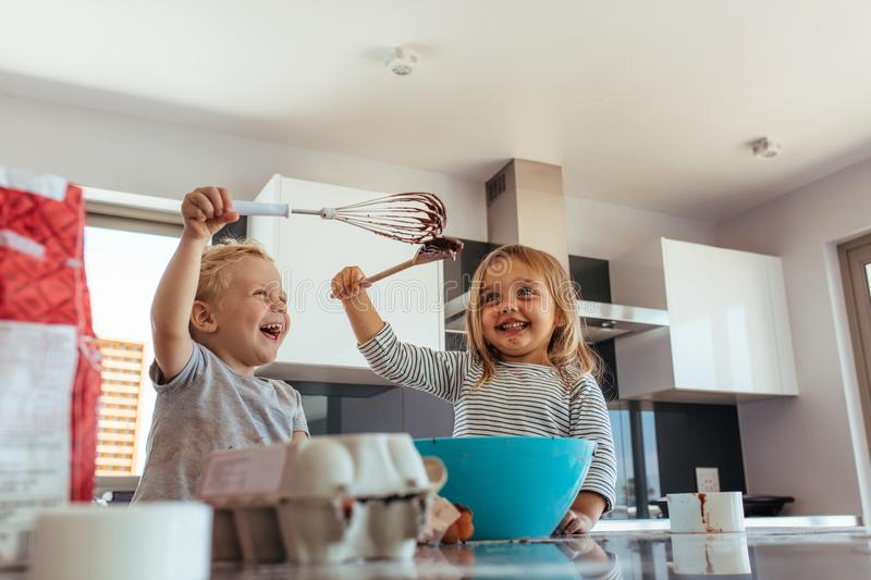 Siblings enjoying baking in kitchen. Cute little boy and girl fighting with whisk and spatula while mixing batter in a bowl. Siblings enjoying baking in home stock image
