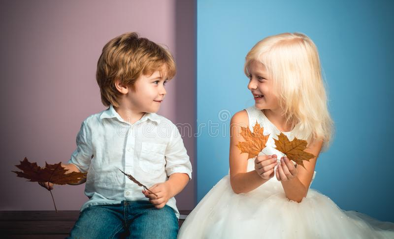 Cute little boy and girl holding leaf on color background. Funny face and happy baby. Children advertise your product. And services. Autumn discounts on baby royalty free stock photos