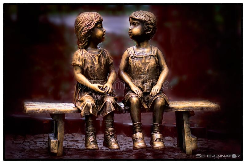 Sculpture little boy and girl sitting on a bench in nature. royalty free stock photo