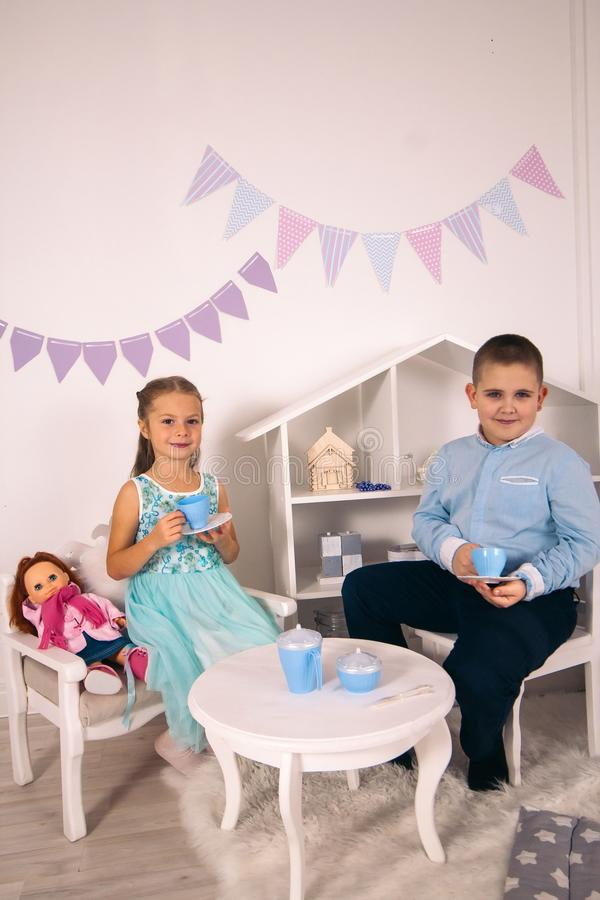 little boy and girl sitting on the table and drinking tea royalty free stock photography