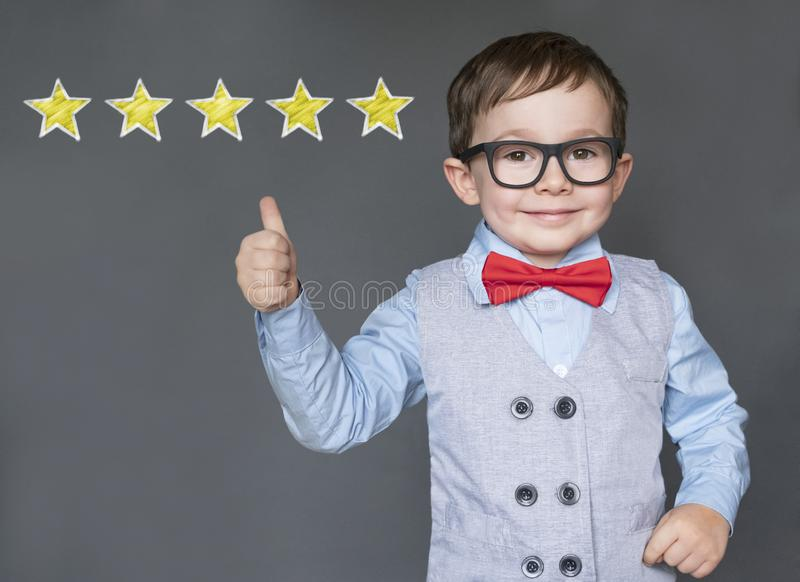 Cute little boy giving thumbs up with 5 stars approved royalty free stock images