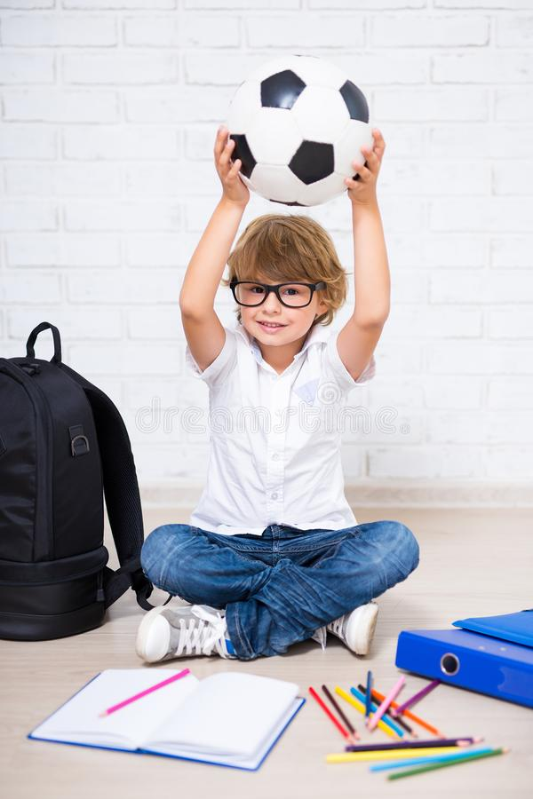 Cute little boy in glasses with school tools and soccer ball stock photo