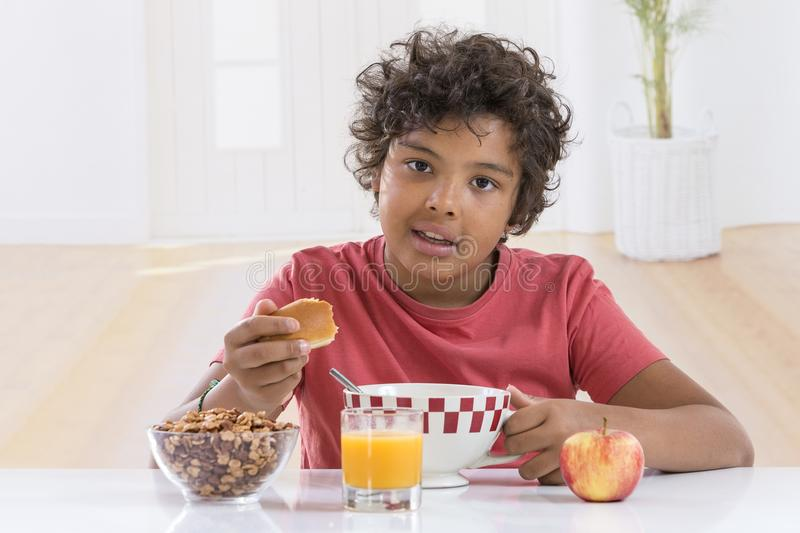 Cute little boy having breakfast at home drinking a large bowl of milk in lblue T-shirt stock photo
