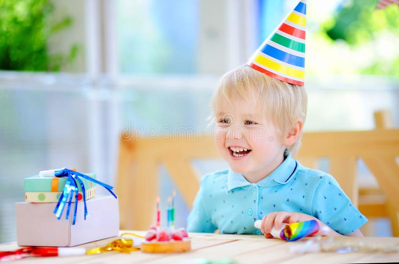 Cute little boy having fun and celebrate birthday party with colorful decoration and cake. Child with sweets, candy, whistle/blower/horn and festive gifts stock photography