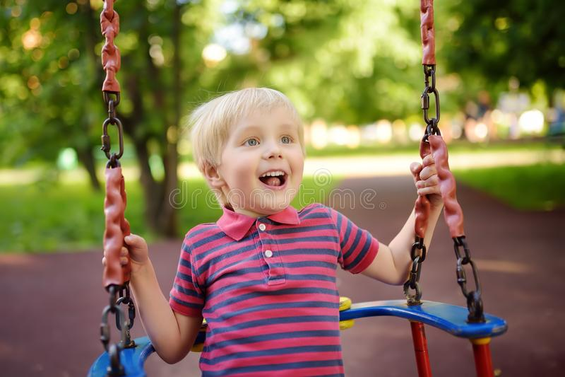 Cute little boy having fun on outdoor playground. Child on swing stock photo