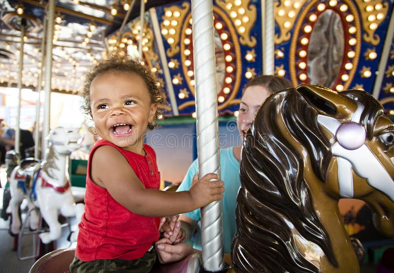 Cute little boy having fun riding on a colorful carnival carousel. Cute mixed race little boy enjoying a ride on a fun carnival carousel. A happy boy Smiling and stock photography