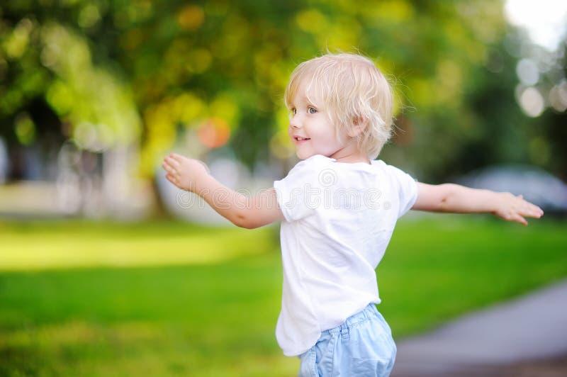 Cute little boy having fun in sunny summer park stock photo