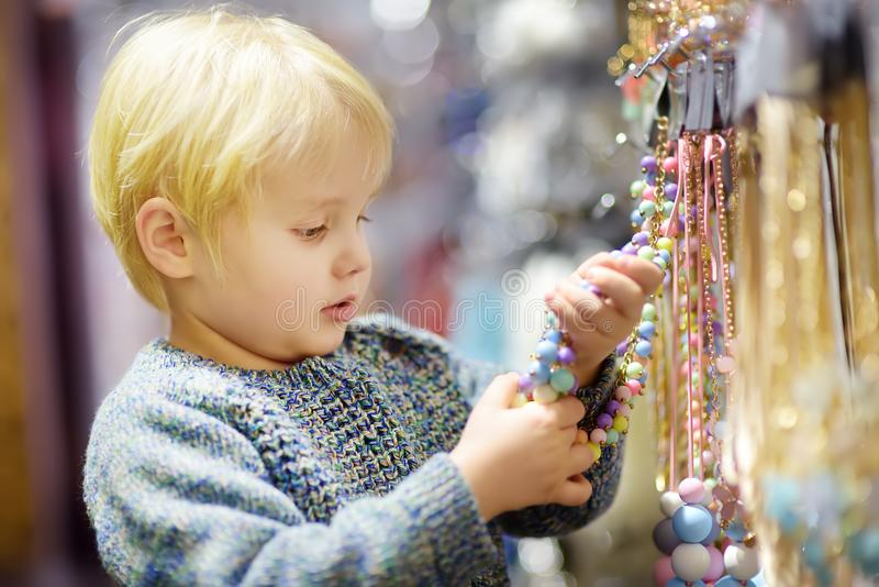 Cute little boy helps his mom to choose jewelry in the accessories store. Fashion for kids. Child with mother in shopping center/mall royalty free stock photos