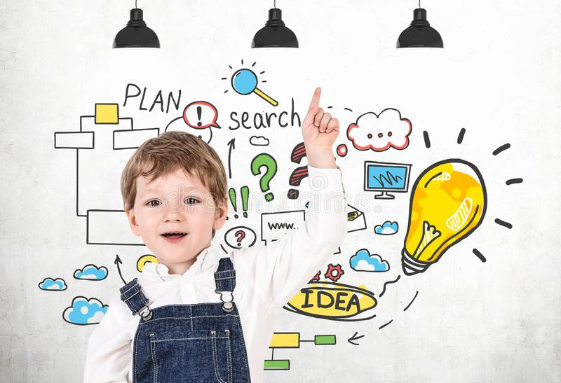 Cute little boy and his business idea. Happy little boy in jeans overalls pointing up standing near white wall with colorful business idea sketch. Concept of royalty free stock photo