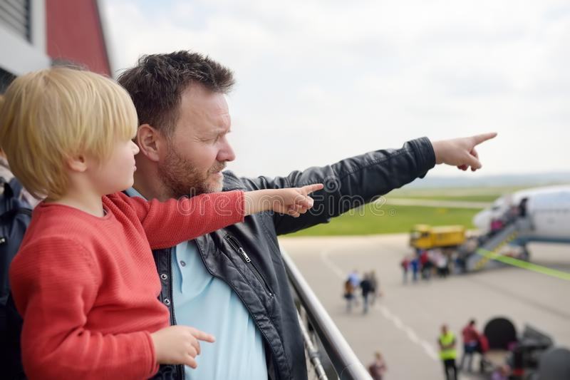 Cute little boy and his father pointing at airplanes on observation deck at airport of small european town before flight. Charming stock photos