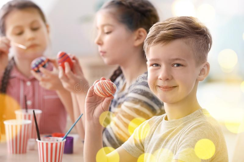 Cute little boy and his friends painting eggs for Easter at home royalty free stock photos
