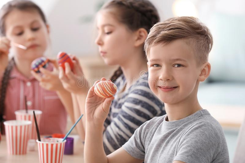 Cute little boy and his friends painting eggs for Easter at home royalty free stock photo