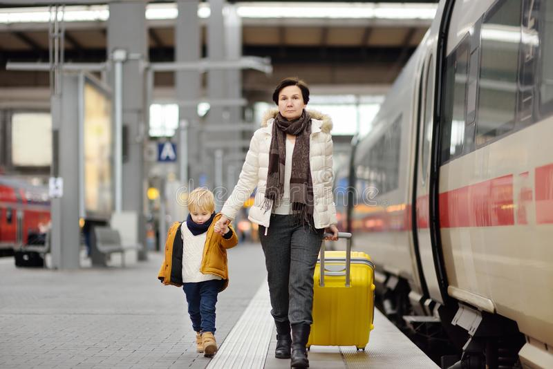 Cute little boy and his grandmother/mother waiting express train on railway station platform. Travel, tourism, winter vacation and family concept. Mature women stock photography