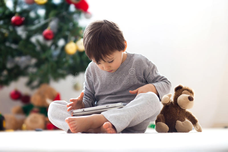 Cute little boy and his monkey toy, playing on tablet. In front of a christmas tree stock images