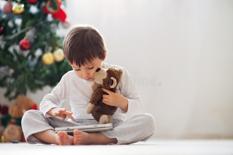 Cute little boy and his monkey toy, playing on tablet. In front of a christmas tree royalty free stock image